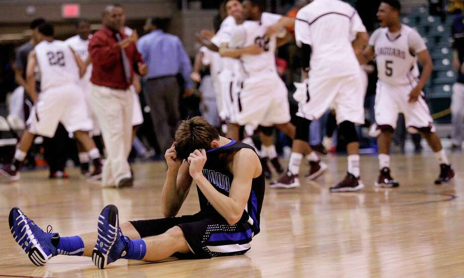 Friendswood's Chris Collins sits on the court after his three-point shot attempt at the buzzer came up short as Beaumont Central celebrates during action from a Class 4A Region III boys basketball semifinal game Friday, Feb. 28, 2014 at the Merrill Center. Beaumont Central won 46-45. Photo: Bob Levey / ©2014 Bob Levey