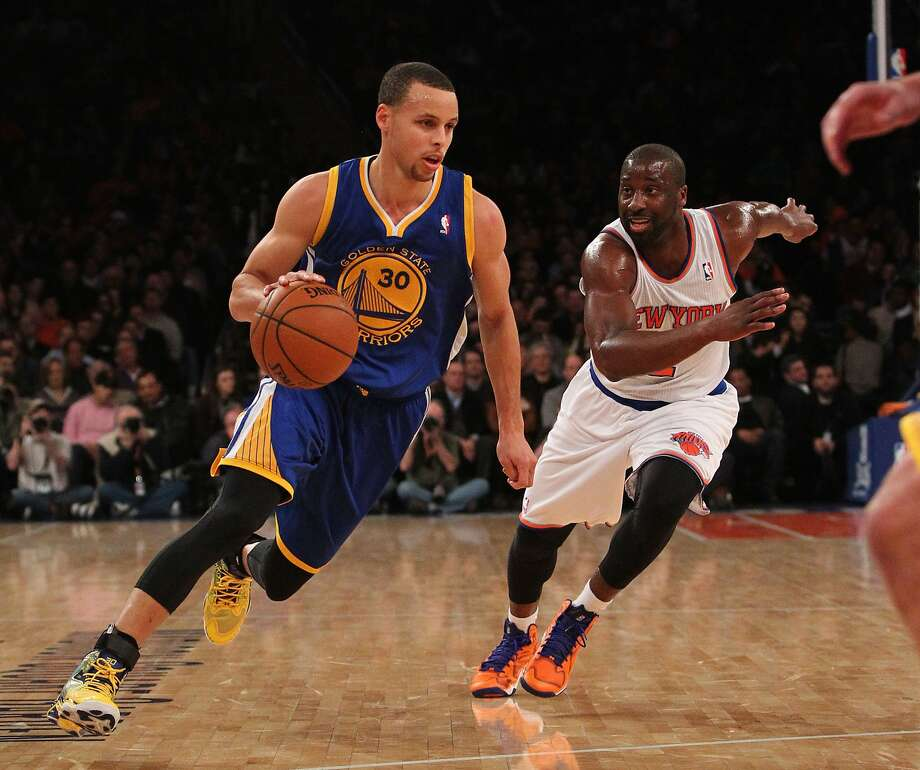 Stephen Curry drives against the Knicks' Raymond Felton. Curry needed only three quarters to record a triple-double. Photo: Noah K. Murray, Reuters