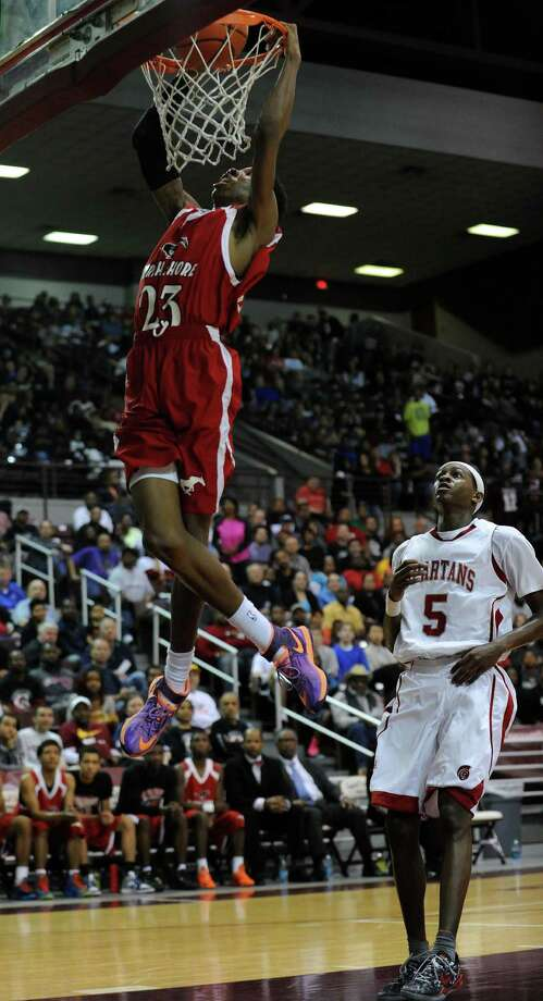 North Shore's Kerwin Roach, left, dunks the ball as Cy-Lakes' De'Aaron Fox looks on during the second half of the Class 5A Region 3 semifinal high school basketball playoff game, Friday, February 28, 2014, at Campbell Center in Houston. Photo: Eric Christian Smith, For The Chronicle