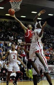 North Shore's Jarrey Foster, center, lays the ball up as Cy-Lakes' De'Aaron Fox defends during the first half of the Class 5A Region 3 semifinal high school basketball playoff game, Friday, February 28, 2014, at Campbell Center in Houston. Photo: Eric Christian Smith, For The Chronicle