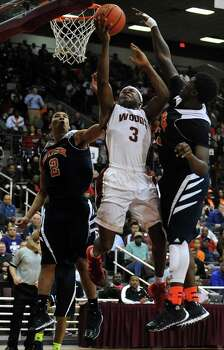 Cy-Woods' JJ Caldwell (3) shoots the ball as Bush's Donald Monroe (2) and Brandon Jones, right, defend during the second half of the Class 5A Region 3 semifinal high school basketball playoff game, Friday, February 28, 2014, at Campbell Center in Houston. Photo: Eric Christian Smith, For The Chronicle