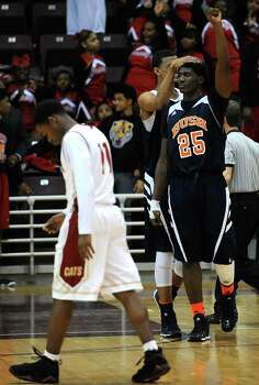 Bush's  Brandon Jones (25) celebrates the Broncos' 60-59 victory over Cy-Woods with teammate Eden Ewing as Cy-Woods' Jordan Houston walks off the court in defeat in the Class 5A Region 3 semifinal high school basketball playoff game, Friday, February 28, 2014, at Campbell Center in Houston. Photo: Eric Christian Smith, For The Chronicle