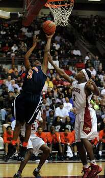 Bush's Brendon Ganaway, left, shoots the ball as Cy-Woods' JJ Caldwell defends during the second half of the Class 5A Region 3 semifinal high school basketball playoff game, Friday, February 28, 2014, at Campbell Center in Houston. Photo: Eric Christian Smith, For The Chronicle