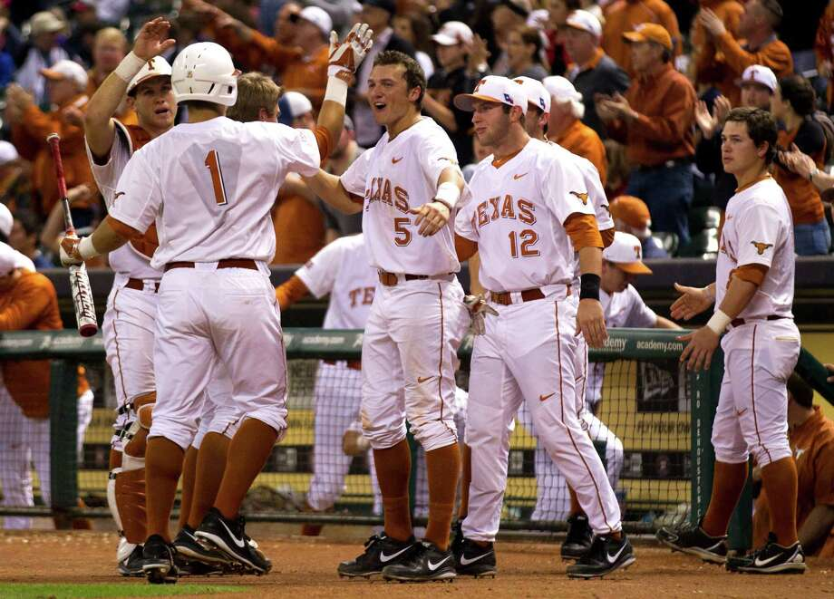 Texas' Tres Barrera (1) works the receiving line after scoring on Ben Johnston's double in the fourth inning of the Longhorns' 2-0 victory over Rice on Friday. Photo: Brett Coomer, Houston Chronicle / © 2014 Houston Chronicle