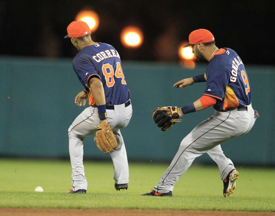 Carlos Correa and Marwin Gonzalez chase a ball hit by Atlanta's Matt Kennelly. Photo: Karen Warren, Houston Chronicle