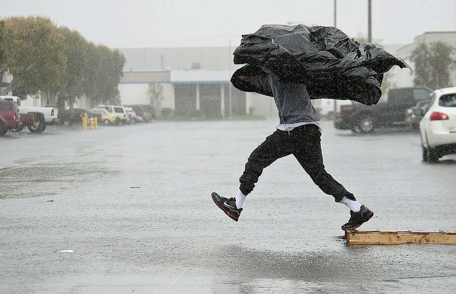 Manufacturing Assembly worker Terry Young, 24, of Rialto, Calif., uses a sheet of plastic to protect himself from a downpour Friday, Feb. 28, 2014, as he jumps a flooded parking lot from a wood pallet to get to a food truck during his break in Anaheim, Calif. The first wave of a powerful Pacific storm spread rain and snow early Friday through much of California, where communities endangered by a wildfire just weeks ago now faced the threat of mud and debris flows. (AP Photo/The Orange County Register, Ken Steinhardt) MAGS OUT; LOS ANGELES TIMES OUT Photo: Ken Steinhardt, Associated Press