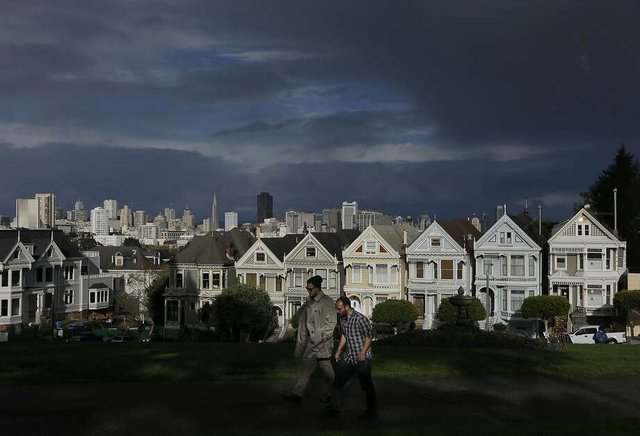 "Two men walk along a path at Alamo Square Park with the ""Painted Ladies,"" a row of historical Victorian homes, and the San Francisco skyline at rear on Friday, Feb. 28, 2014. California was lashed Friday by heavy rains that the parched state so desperately needs, though with the soaking came familiar problems: traffic snarls, power outages and the threat of mudslides. Even with rainfall totals exceeding 6 inches in some places by midday, the powerful Pacific storm did not put a major dent in a drought that is among the worst in recent California history. (AP Photo/Jeff Chiu) Photo: Jeff Chiu, Associated Press"