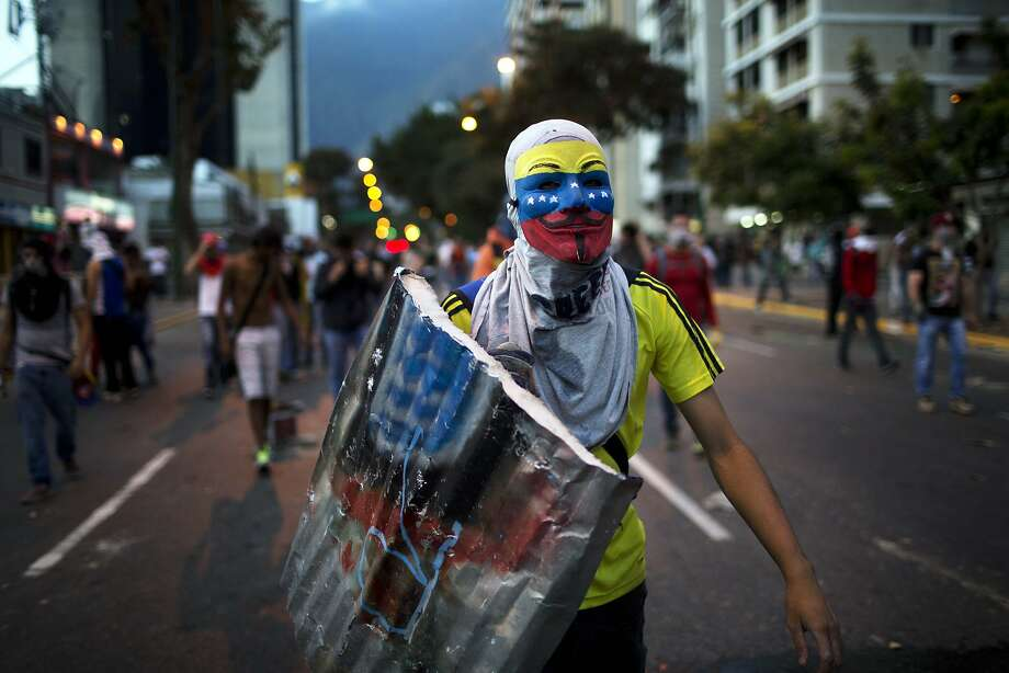 Anti-government demonstrator walks towards riot policemen during a protest in Caracas, Venezuela, Friday, Feb. 28, 2014. The start of a weeklong string of holidays leading up to the March 5 anniversary of former President Hugo Chavez's death has not completely pulled demonstrators from the streets as the government apparently hoped. President Nicolas Maduro announced this week that he was adding Thursday and Friday to the already scheduled long Carnival weekend that includes Monday and Tuesday off, and many people interpreted it as an attempt to calm tensions. (AP Photo/Rodrigo Abd) Photo: Rodrigo Abd, Associated Press
