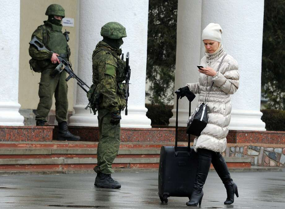 """TOPSHOTS Unidentified armed men patrol outside of Simferopol airport, on February 28, 2014. Ukraine accused today Russia of staging an """"armed invasion"""" of Crimea and appealed to the West to guarantee its territorial integrity after pro-Moscow gunmen took control of the peninsula's main airport.AFP PHOTO / VIKTOR DRACHEVVIKTOR DRACHEV/AFP/Getty Images Photo: Viktor Drachev, AFP/Getty Images"""