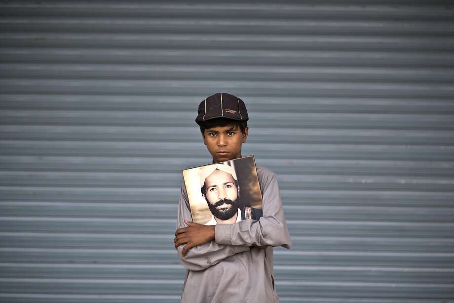 Ali Haider, 10, poses for a portrait holding a photograph of his father, who went missing on July 14, 2010, while he and other relatives take a break from a long march protest, in Rawalpindi, Pakistan, Friday, Feb. 28, 2014. Ten-year-old Ali Haider has spent the last four months of his life walking across the breadth of Pakistan in an effort to find out what has happened to his father who has been missing since 2010. Haider is the youngest of two dozen activists from the impoverished southwestern province of Baluchistan who walked roughly 3,000 kilometers (1,860 miles) to the capital of Islamabad to draw attention to alleged abductions of their loved ones by the Pakistani government. (AP Photo/Muhammed Muheisen) Photo: Muhammed Muheisen, Associated Press