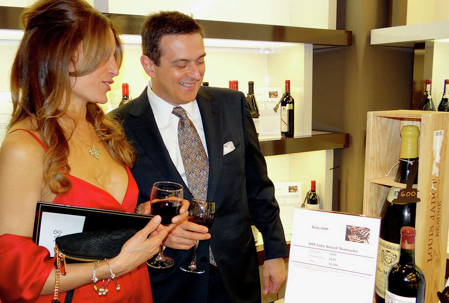 Carol Langeland of Fairfield and Bill Brown of Wilton look at silent auction wines offered at Near & Far Aid's Spring Gala. Photo: Mike Lauterborn / Westport News contributed