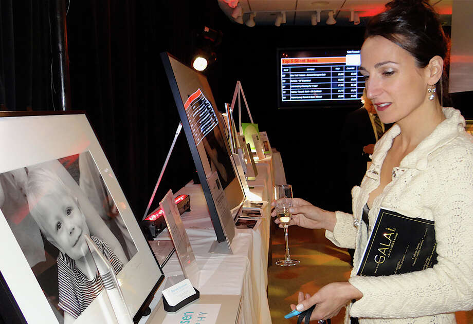 Katia Mead of Fairfield browses silent auction items at Near & Far Aid's Spring Gala on Friday night. Photo: Mike Lauterborn / Westport News contributed