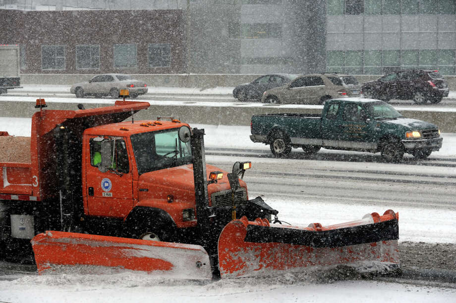 A state Department of Transportation truck plows snow along I-95 in Bridgeport during a storm in January. This winter is the first season the DOT has used a magnesium chloride slurry on highways in advance of storms. Truckers say the corrosive mixture is causing  undercarriage and brake line corrosion . Photo: Ned Gerard / Connecticut Post