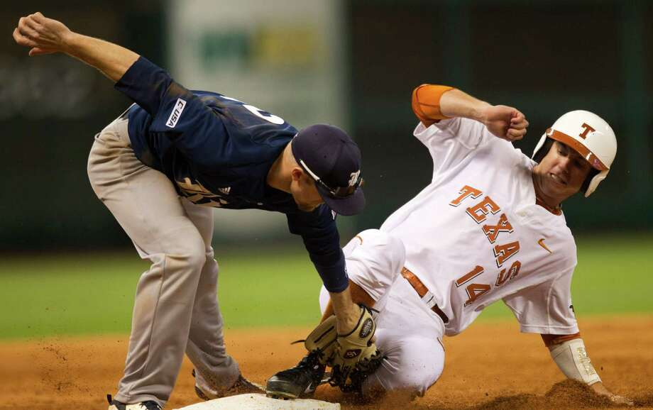Texas outfielder Ben Johnson (14) slides under the tag of Rice third baseman Shane Hoelscher during the fourth inning of the Houston College Classic at Minute Maid Park dow}, Feb. 28, 2014, in Houston. Photo: Brett Coomer, Houston Chronicle / © 2014 Houston Chronicle