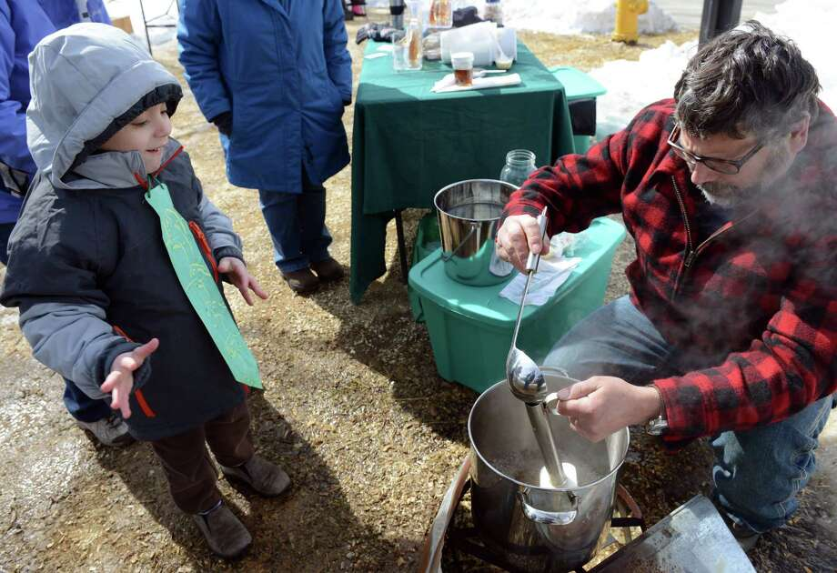 Six-year-old Gaetan Grech, of Bridgeport, eagerly awaits a taste of fresh maple syrup from Greg Karas, of Ansonia, Saturday, Mar. 1, 2014, during the Ansonia Nature Center's Maple Festival in Ansonia, Conn.  Karas, a back yard syrup maker, started boiling his sap around 10 am and the batch was ready for tasting around 12:30. Photo: Autumn Driscoll / Connecticut Post