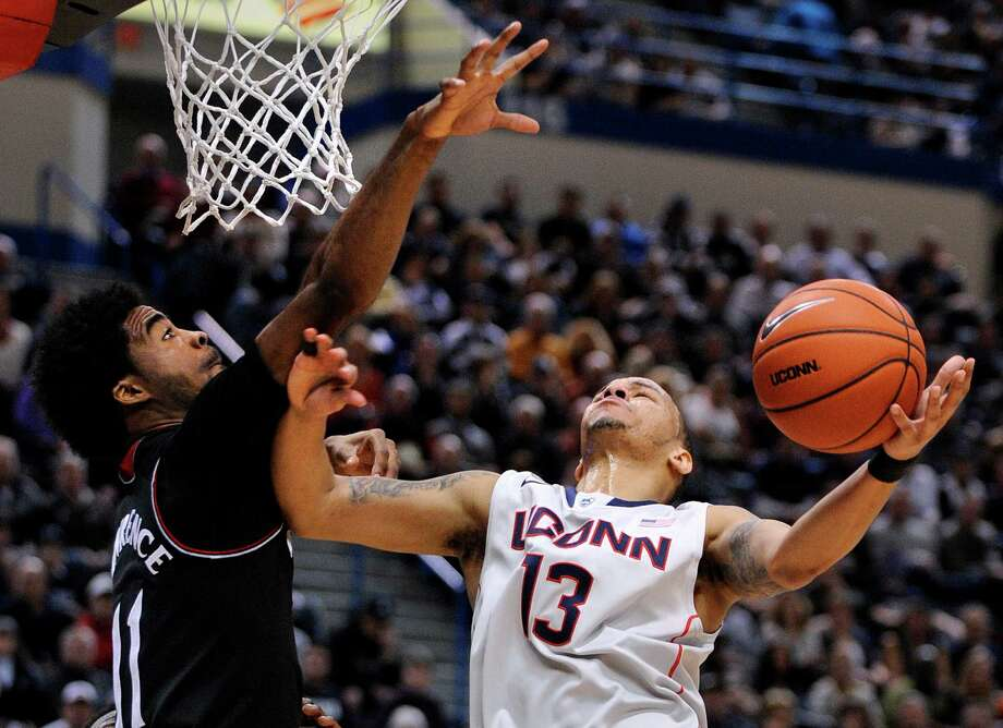 Connecticut's Shabazz Napier (13) is fouled by Cincinnati's Jermaine Lawrence (11) during the second half of an NCAA college basketball game in Hartford, Conn., Sunday, March 1, 2014. Napier scored a game-high 18 points and had 11 rebounds in his team's 51-45 victory. Photo: Fred Beckham, AP / Associated Press