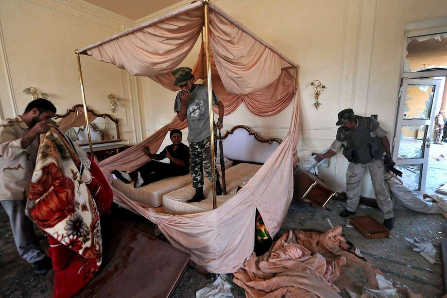 Another brutal dictator that was overthrown was Mummar Gaddafi of Libya.  In this photo, Libyan National Transitional Council (NTC) fighters search a room at ousted Libyan leader Mummar Gaddafi's Sirte palace, partly destroyed by NATO air raids in 2011.  Photo: Aris Messinis, AFP/Getty Images