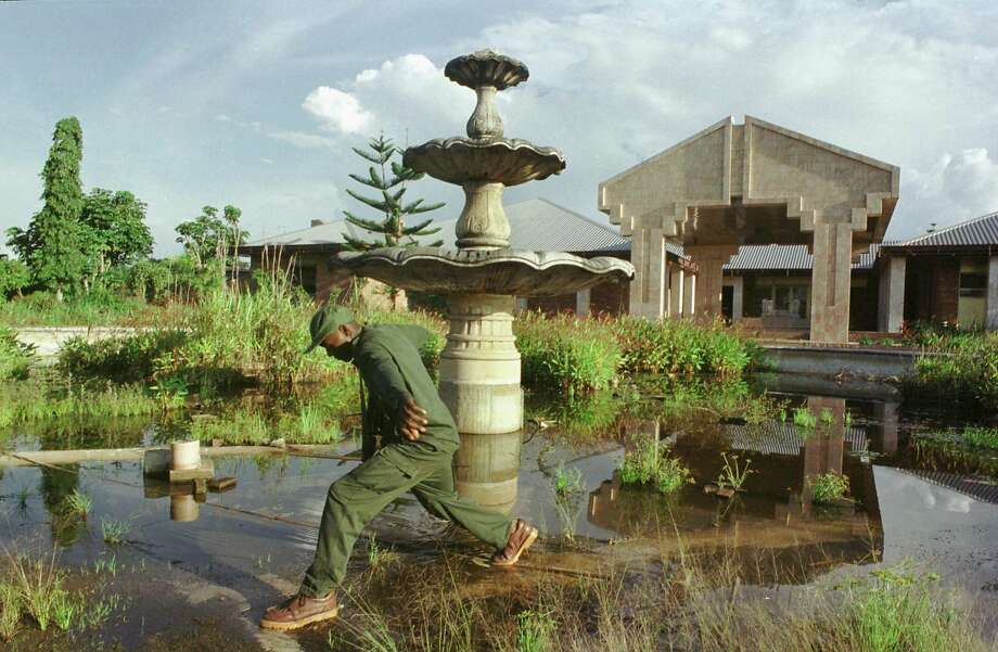 A soldier with the rebel Movement for the Liberation of Congo (MLC) steps across an overgrown fountain in front of one of the late Mobutu Sesse Seko's palaces September 15, 2000 in Gbadolite, Congo. All three of the elaborate palaces in Gbadolite have long been looted. Photo: Tyler Hicks