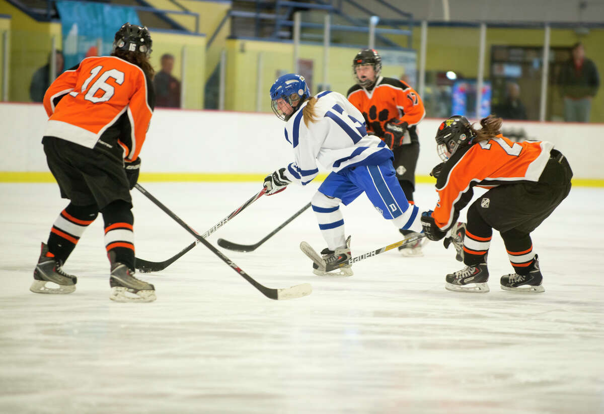 Darien's Sage Thacher (13) controls the puck during the FCIAC championship girls ice hockey game against Ridgefield High School at Terry Conners Rink in Stamford on Saturday, Mar. 1, 2014