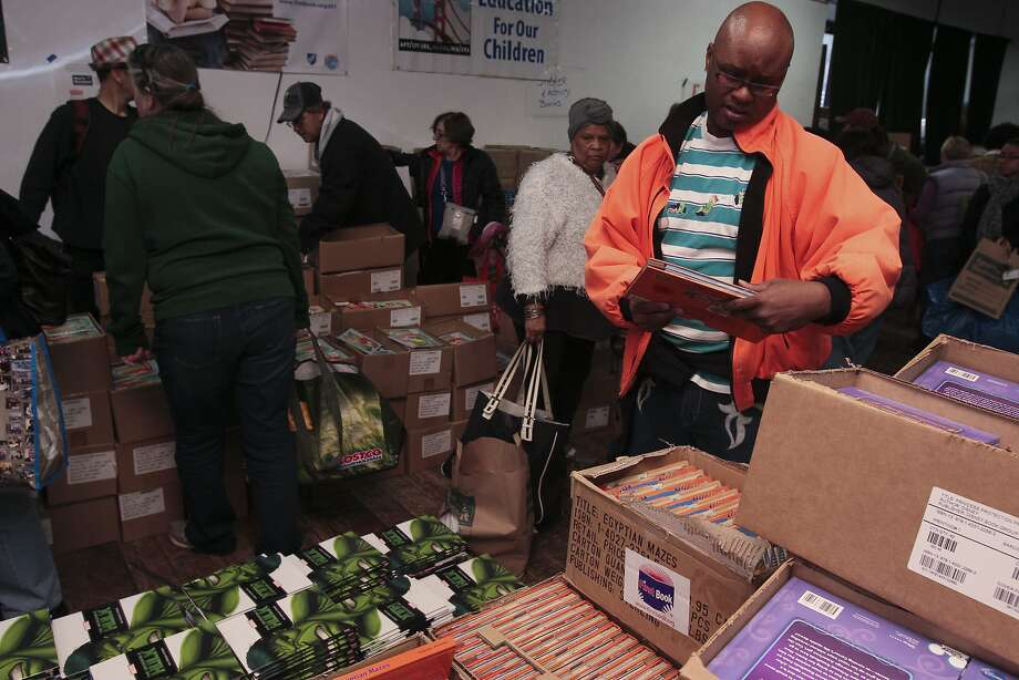 Paul Morgan (right) looks through some of the books. Photo: Andre Zandona, The Chronicle