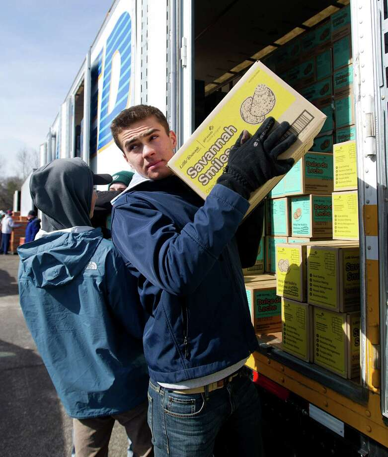 Ross Poulley helps load Savannah Smiles into a van as volunteers pick up their cookie orders for Girl Scout troops in Fairfield County on Saturday, March 1, 2014. Photo: Lindsay Perry / Stamford Advocate