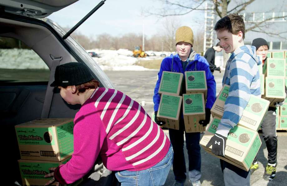 Volunteers help load Thin Mints into a van as volunteers pick up their cookie orders for Girl Scout troops in Fairfield County on Saturday, March 1, 2014. Photo: Lindsay Perry / Stamford Advocate