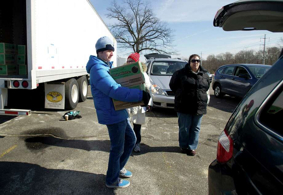 Matthew Payne helps load Thin Mints into a van as volunteers pick up their cookie orders for Girl Scout troops in Fairfield County on Saturday, March 1, 2014. Photo: Lindsay Perry / Stamford Advocate