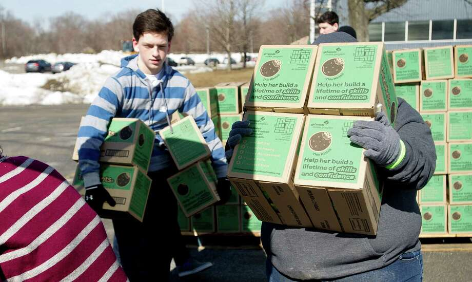 Volunteers, including Maria Signore, right, load Thin Mints into a van as volunteers pick up their cookie orders for Girl Scout troops in Fairfield County on Saturday, March 1, 2014. Photo: Lindsay Perry / Stamford Advocate