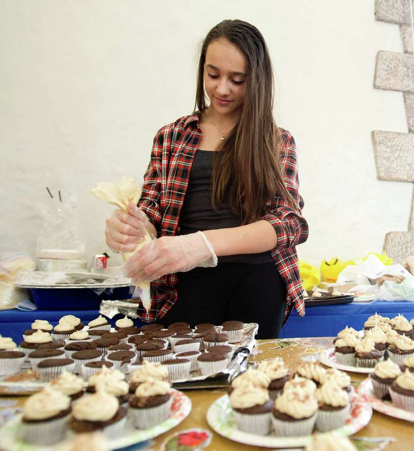 Marissa Young of Stamford ices her devil's chocolate cupcakes with maple buttercream frosting during the teen cooking competition as part of the Maple Sugar Festival at the Stamford Museum and Nature Center on Saturday, March 1, 2014. Photo: Lindsay Perry / Stamford Advocate