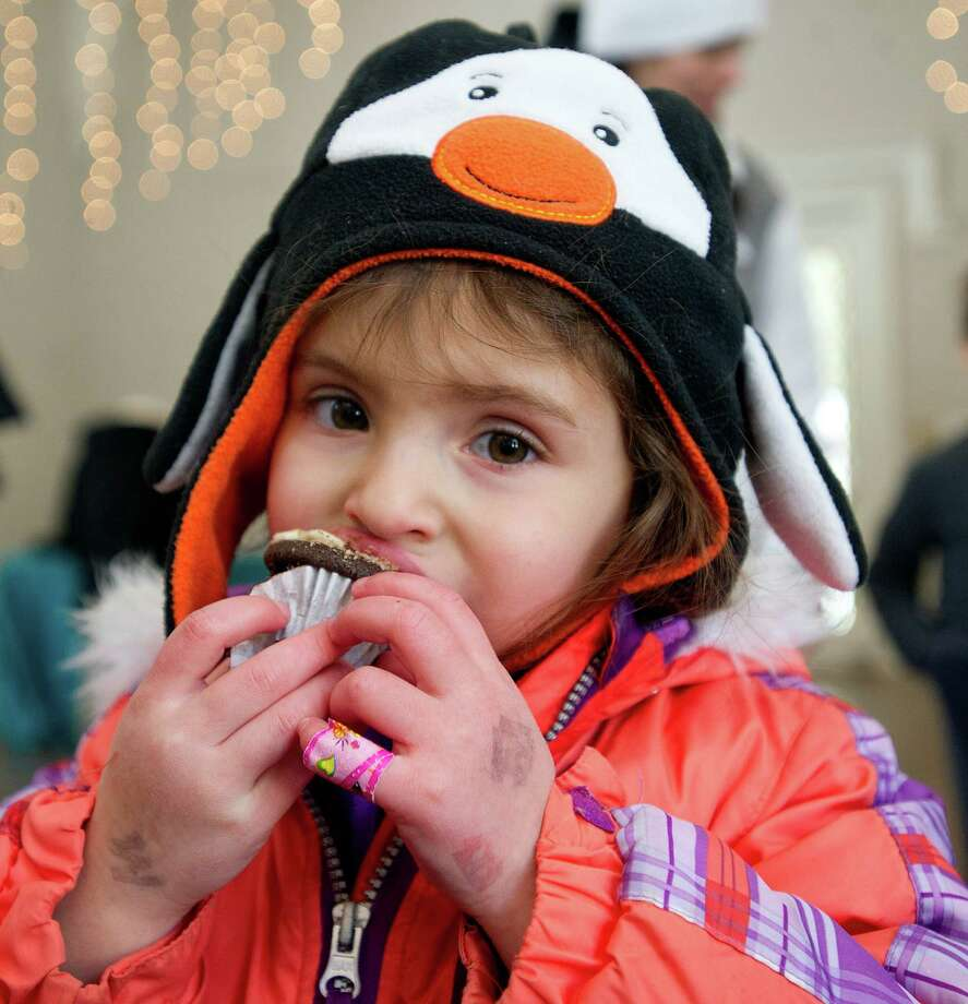 May Simone Avidan, 3, tries devil's chocolate cupcakes with maple buttercream frosting made by Marissa Young of Stamford during the teen cooking competition as part of the Maple Sugar Festival at the Stamford Museum and Nature Center on Saturday, March 1, 2014. Photo: Lindsay Perry / Stamford Advocate