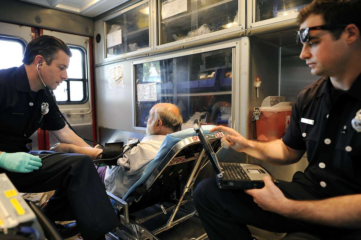 EMT Alex Lamond, right, and Paramedic Josh Smith work on a diabetic patient, who called for help because he was feeling weak and dizzy, in the back of their ambulance, in San Francisco, CA Saturday, March 1, 2014.