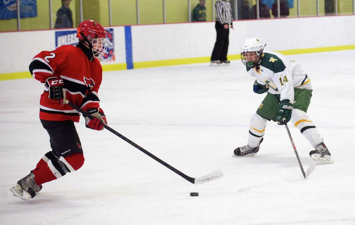 Greenwich's Kevin Piotrzkowski, left, controls the puck during Saturday's FCIAC quarterfinal against Trinity Catholic at Terry Conners Rink in Stamford, Conn., on March 1, 2014.