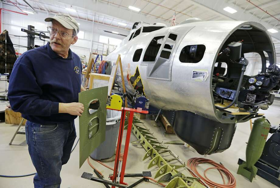 Project manager Randy Kemp works on a panel for the engine housing of a B-17 World War II bomber being built with salvaged and fabricated parts at the Champaign Aviation Museum. Photo: Al Behrman, Associated Press