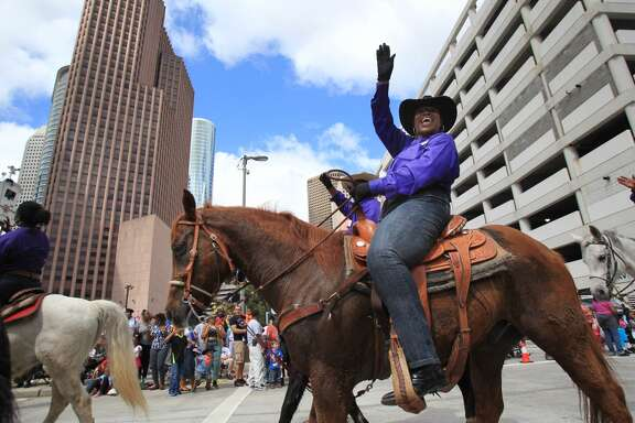Members of the Prairie View Trail Ride wave to the crowd during the 76th Annual Houston Rodeo Parade gets started on Saturday, March 1, 2014, in Houston. ( Mayra Beltran / Houston Chronicle )