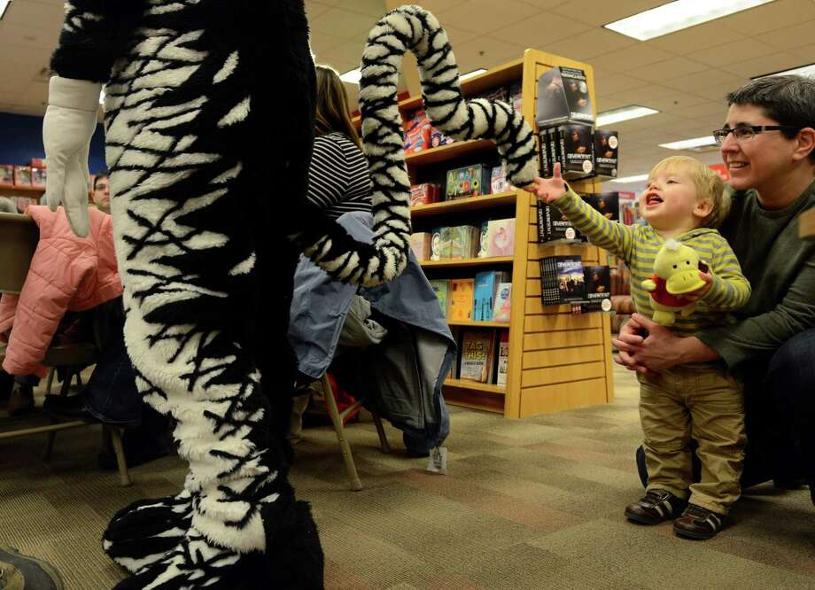 Jeannine Raymond, of Fairfield, holds one-year-old son Oliver as he reaches for the tail of the Cat In The Hat during a story time event to celebrate Read Across America Saturday, Mar. 1, 2014, at the Fairfield University Bookstore in downtown Fairfield, Conn. Photo: Autumn Driscoll / Connecticut Post