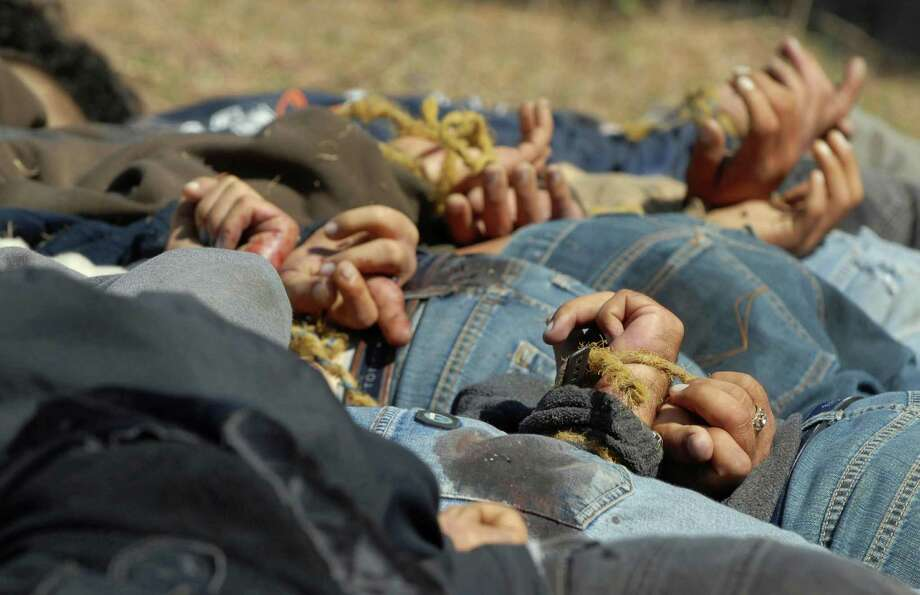 "FILE - In this Dec. 4, 2008, file photo, bodies from a total of 13 bullet-ridden men, with their hands tied behind their backs, victims of the drug war involving Joaquin ""El Chapo"" Guzman's Sinaloa cartel, lie in a field near the town of San Ignacio in the pacific state of Sinaloa, Mexico. Guzman and his cohorts waged an increasingly bloody war over the year with rival gangs. (AP Photo/File) Photo: Anonymous, STR / AP"