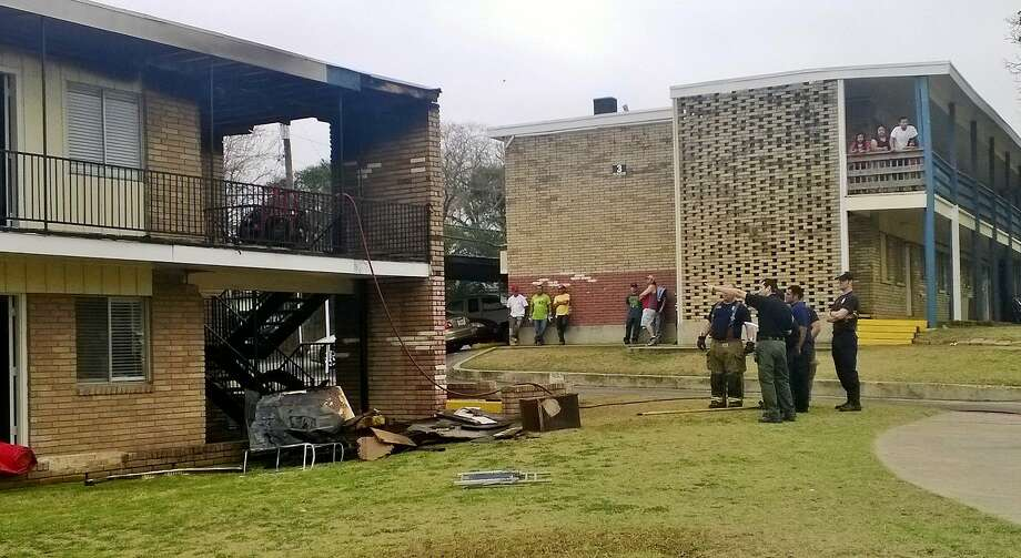 Firefighters examine damage caused by a two-alarm fire early Saturday at an apartment complex on the 3200 Block of Bolmore Drive. Photo: Jacob Beltran