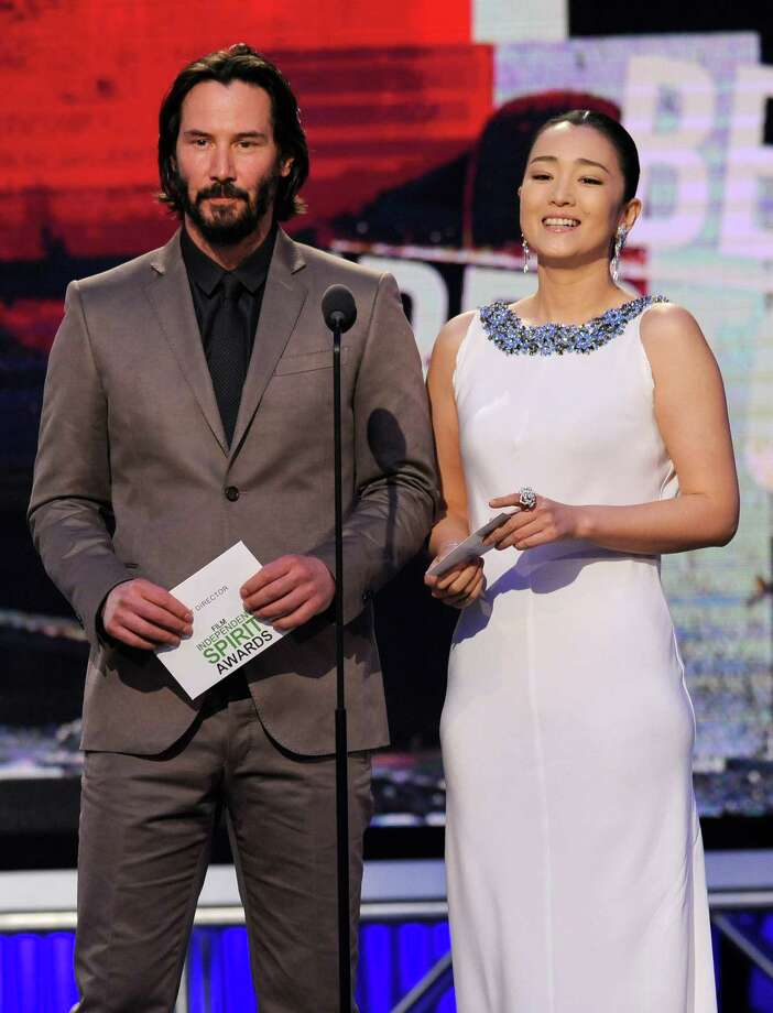 Keanu Reeves, left, and Gong Li speak on stage. Photo: Chris Pizzello, Chris Pizzello/Invision/AP / Invision