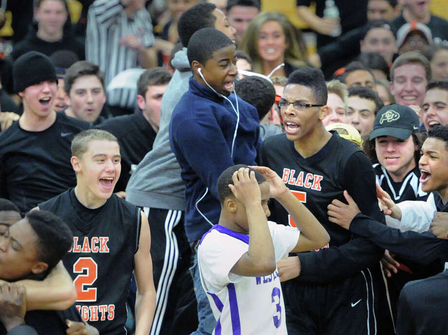 Stamford High School basketball players Jay Devito (#2), left, and Kweshon Askew (#5), right, celebrate their one point victory over cross-town rival Westhill as Westhill's CJ Donadson (#3), foreground, puts his hands to his head in disbelief at the end of their FCIAC Boys Basketball Quarterfinal game between Stamford High School and Westhill High School at Fairfield Ludlowe High School, Fairfield, Conn., Saturday, March 1, 2014. Stamford advanced by defeating Westhill, 55-54. Photo: Bob Luckey / Greenwich Time