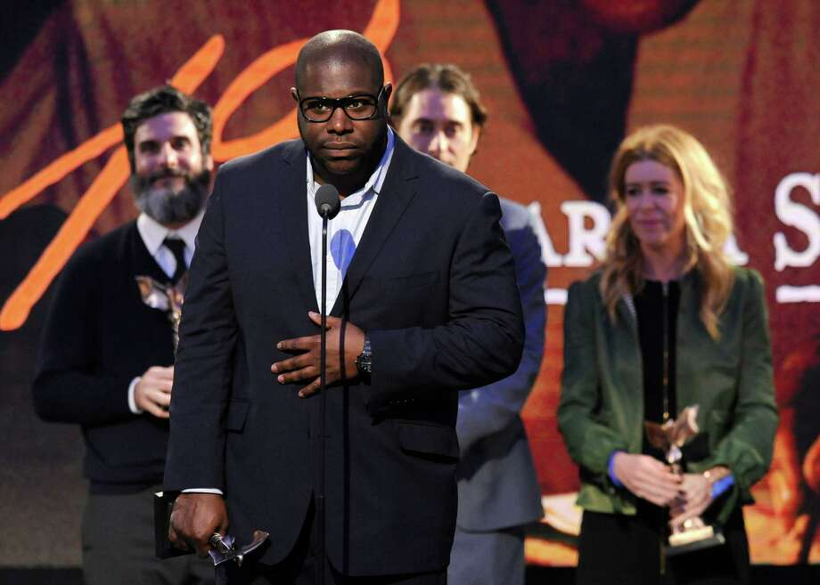 "Steve McQueen, second from left, accepts the best feature award for ""12 Years a Slave"" along with, from left, Anthony Katagas, Jeremy Kleiner and Dede Gardner on stage. Photo: Chris Pizzello, Chris Pizzello/Invision/AP / Invision"