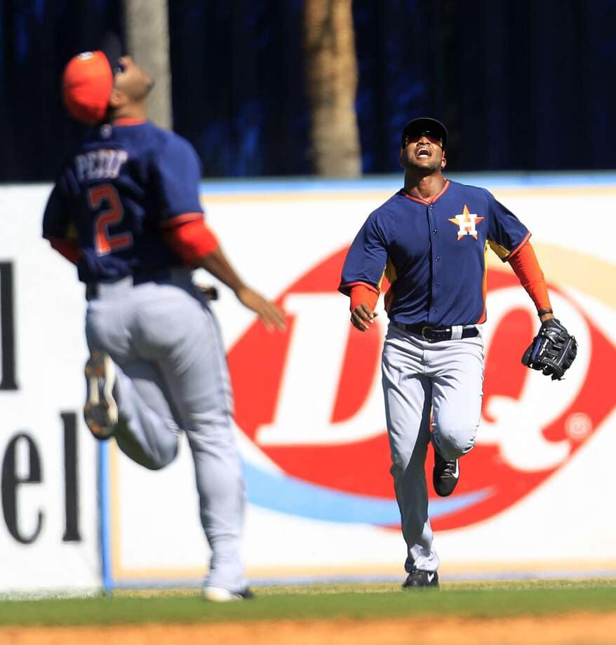 Domingo Santana and Gregorio Petit run towards a flyout by Detroit's Austin Jackson. Photo: Karen Warren, Houston Chronicle