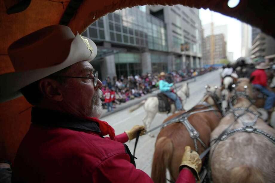 Floyd Stewart holds the reigns for one of the many wagons parading with the Sam Houston Trail Ride during the 76th Annual Houston Rodeo Parade. Photo: Mayra Beltran, Houston Chronicle / © 2014 Houston Chronicle