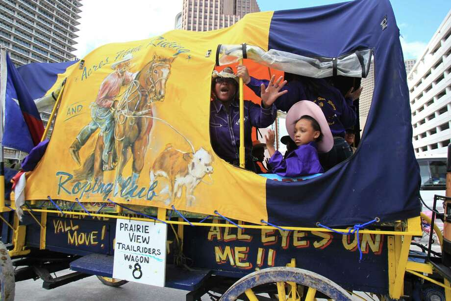 Members of the Acres Home Riding and Roping Club join the Prairie View Trail Ride waving to the crowd during the 76th Annual Houston Rodeo Parade. Photo: Mayra Beltran, Houston Chronicle / © 2014 Houston Chronicle