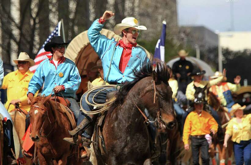 A cowboy with the Sam Houston Trail Ride cheers for the crowd during the 76th Annual Houston Rodeo P