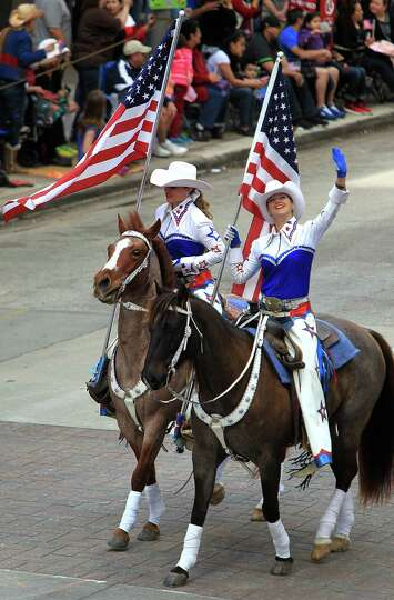 Cowgirls wave to spectators viewing the 76th Annual Houston Rodeo Parade from a partaking structure