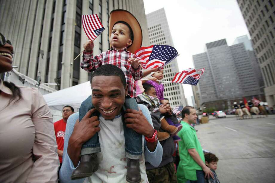 Tyrelle Cheeves carries son Tyre Cheeves while the 76th Annual Houston Rodeo Parade gets started on Saturday, March 1, 2014, in Houston. Photo: Mayra Beltran, Houston Chronicle / © 2014 Houston Chronicle