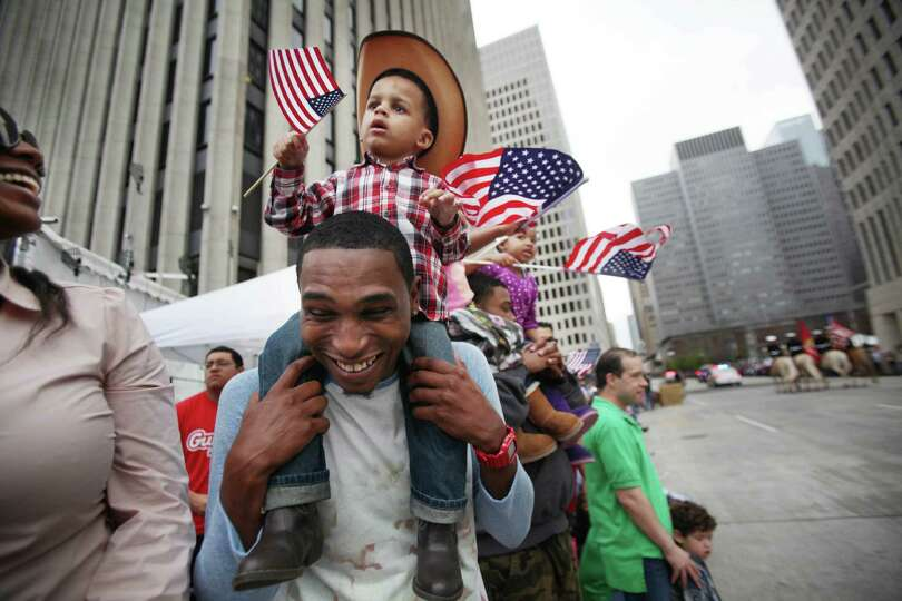 Tyrelle Cheeves carries son Tyre Cheeves while the 76th Annual Houston Rodeo Parade gets started on
