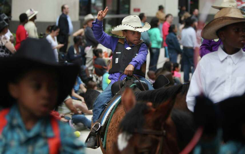 A young member of the Prairie View Trail Ride waves to the crowd.