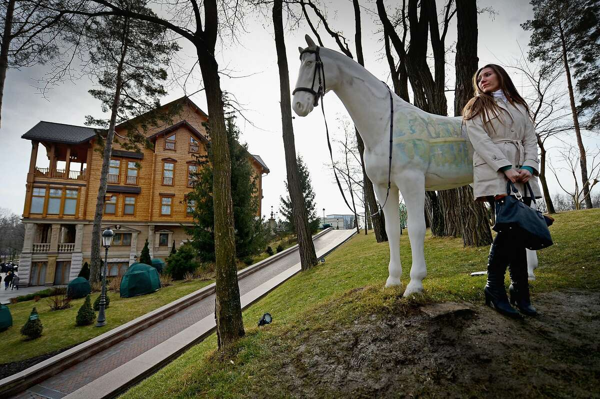 A woman stands near a sculpture of a horse around President Viktor Yanukovych's Mezhyhirya estate, which was abandoned by security in Kiev, Ukraine. Citizens of the country were able to view first-hand the excesses of their former President.