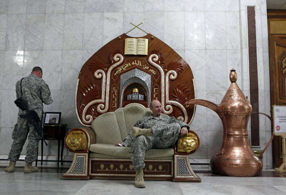 A U.S. Army soldier relaxes on an armchair, believed to have belonged to Iraq's late dictator, Saddam Hussein, at al-Faw Palace on the western outskirts of Baghdad, Iraq in 2009. Photo: Khalid Mohammed